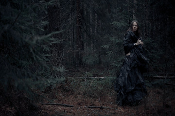 man with long hair in the dark forest