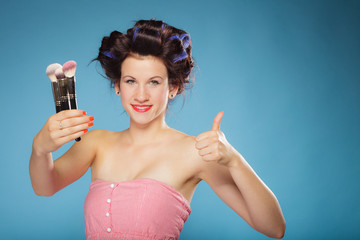 woman in hair rollers holds makeup brushes