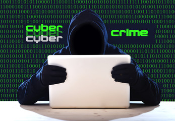 hacker in hood mask with computer hacking system in cyber crime