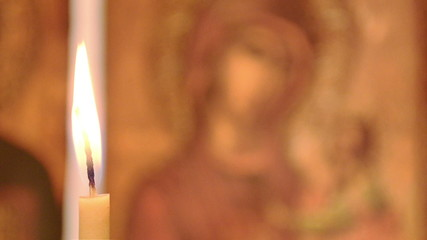 Candle in the background of the icon of the Virgin Mary