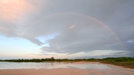 Full rainbow over flat subtropical terrain and lagoon