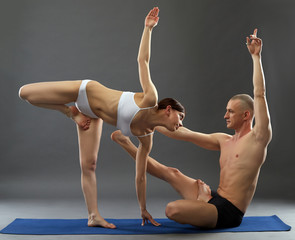 Paired yoga. Image of people exercising in studio