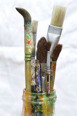 Paint brushes. Old paint brushes in a glass bottle.