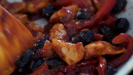 Cooking, mixing chicken, pepper and olives on pan, closeup