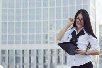 Successful business woman with folder on background skyscraper.