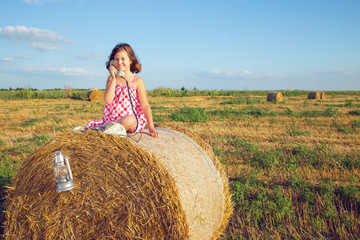 The girl sitting on a bale of hay in the field and phones