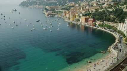 Panning shot of people on beach and moored boats / Villafranche, France