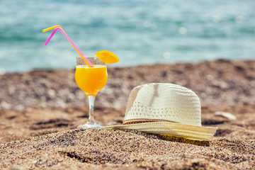 Cocktails and hat for the beach on beach background