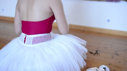 young ballerina preparing for dance - woman adjusts hair