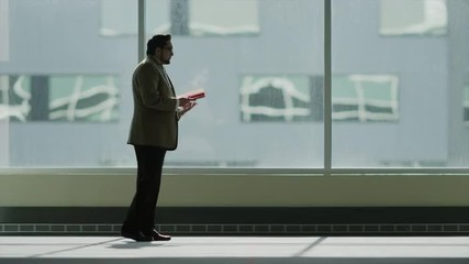 Medium shot of businessman walking and using digital tablet / Provo, Utah, United States,