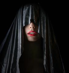 Portrait of beautiful woman in cape on dark background.