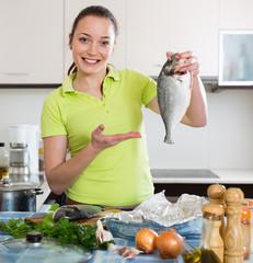 Woman cooking fish at home.
