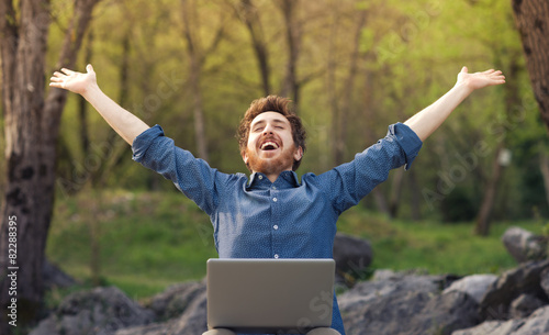 Happy hipster with laptop in the forest - 82288395