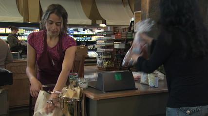 grocery clerk bagging groceries in a reusable bag