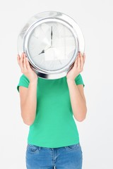 Brunette holding wall clock and hiding her face