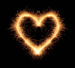 Bright romantic love heart drawn with sparkles isolated on black