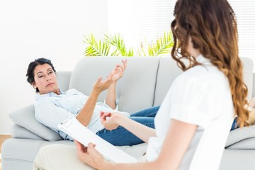 Therapist listening her patient and taking notes