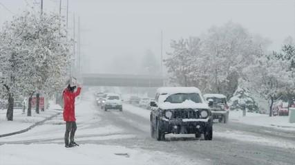 Snow falling on woman crossing busy urban street / Orem, Utah, United States,