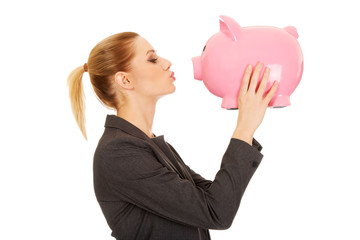 Happy businesswoman kissing a piggybank.