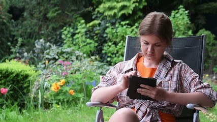 young woman reading e-book in garden