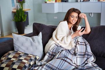frau sitzt auf einer couch mit einem mobiltelefon