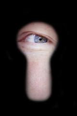 eye looking at you through door keyhole