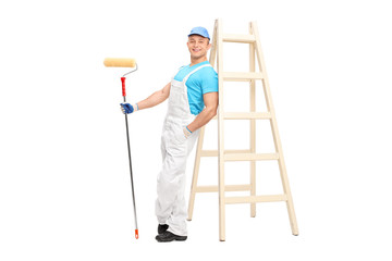 Young male decorator holding a paint roller