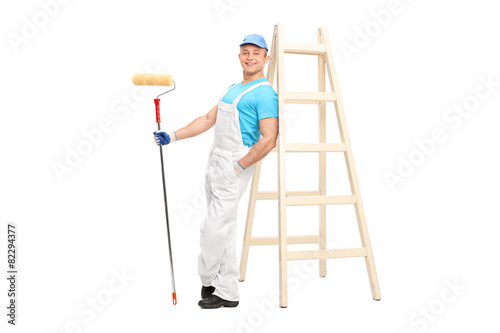 Young male decorator holding a paint roller - 82294377