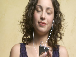 Woman with mP3 player listening to music and dancing