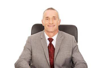 Mature businessman sitting on armchair
