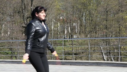 young beautiful woman jumping rope in a city park closeup