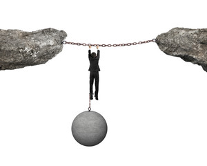 Businessman shackled by ball hanging on iron chains link cliffs