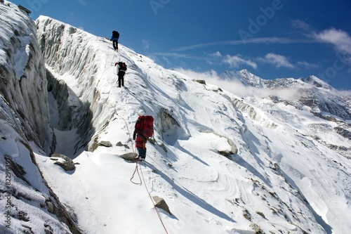 Fotobehang Nepal group of climbers on rope on glacier