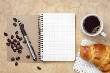 Notebook, croissant and coffee