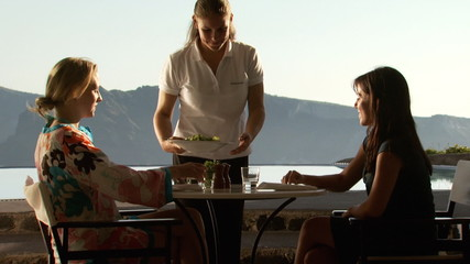 Two women dining outdoors at a scenic restaurant