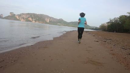 young european girl run along beach at sunrise