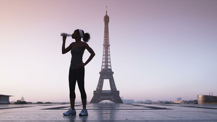 jogger drinking water in front of the Eiffel tower