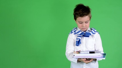 child boy holds textbooks and smiles to camera - green screen