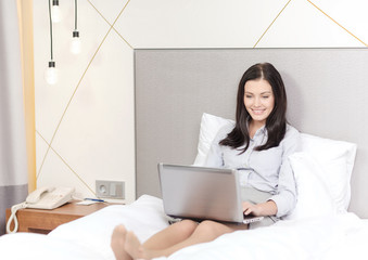 happy businesswoman with laptop in hotel room