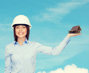 businesswoman in helmet holding house on palm