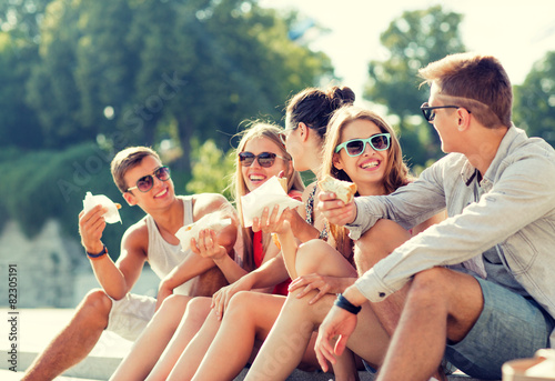 group of smiling friends sitting on city square - 82305191