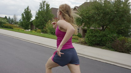 Close up slow motion tracking shot of woman running in suburban neighborhood / Cedar Hills, Utah, United States