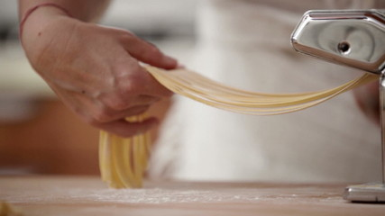 Adult woman cutting and rolling noodles.