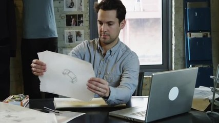 MS Young man working in office holding drawing against laptop / Salt Lake City,Utah,USA