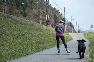Woman is skating on rollerblades beside her dog outdoors.
