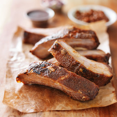 grilled barbecued ribs cut into pieces on wooden cutting board