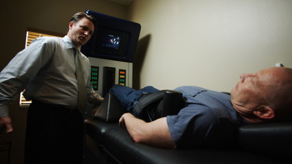 chiropractor with a patient on a machine