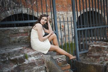 Девушка сидящая на руинах