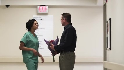 MS Nurse showing direction to man with flowers in hospital corridor / Payson, Utah, USA