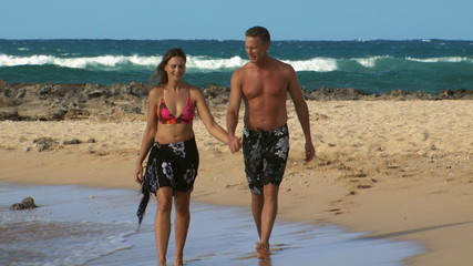 Couple walking on beach smiling and holding hands